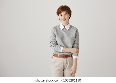 Portrait of cute redhead woman with short stylish haircut and freckles standing unconfidently over gray background in trendy outfit. Girl tries to give speech in front of audience for first time