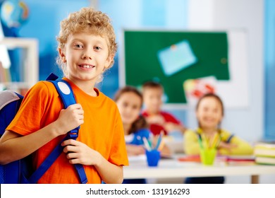 Portrait of cute schoolboy with backpack looking at camera with his classmates on background