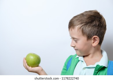 Portrait of a cute schoolboy with blue backpack and green apple on a white background