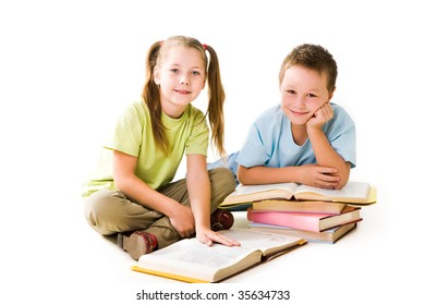 Portrait of cute schoolchildren looking at camera during reading books