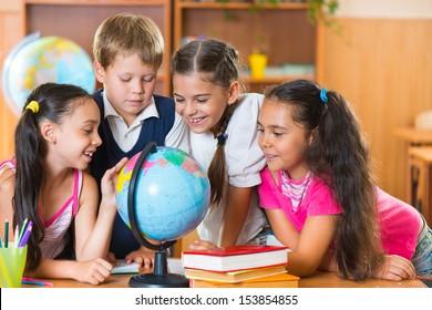 Portrait of cute schoolchildren looking at globe in classroom