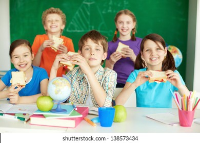 Portrait of cute schoolchildren with sandwiches looking at camera in classroom