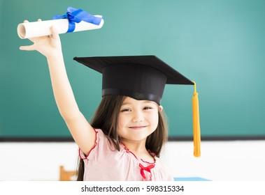Portrait of  cute schoolgirl with graduation hat in classroom