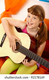 Portrait of cute schoolgirl with guitar, laughing at camera.?