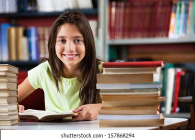 Portrait of cute schoolgirl smiling while sitting with stack of books at table in library