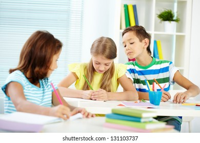 Portrait of cute schoolkids drawing at lesson
