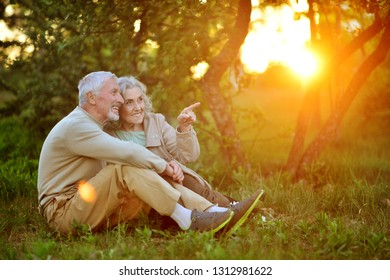 Portrait of cute senior couple sitting outdoors
