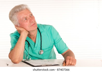 portrait of a cute senior doctor at table