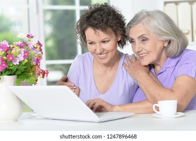 Portrait of cute senior woman with daughter using laptop