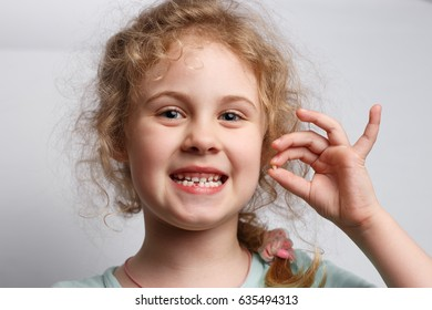 Portrait of cute six years girl losing her first milk tooth.