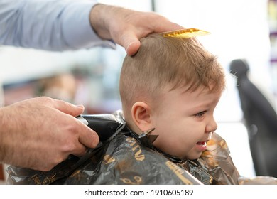 Portrait of cute small baby boy in barber shop getting his first haircut. Infant boy scared and crying during hairdresser cutting his hairs. Hairdressers hands making hairstyle for 8 month child boy.
