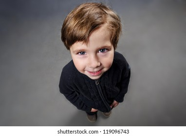Portrait of cute small boy looking up.