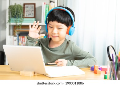 Portrait of a cute and smart asian student boy wearing headphone wave his hand to device camera and smile, using tablet computer to join online classroom from home during Covid-19 pandemic. New normal
