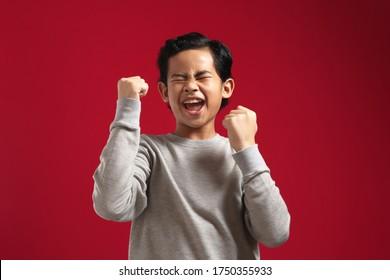 Portrait eines süßen, jungen Asiaten Jungen mit grauem Hemd zeigt Gewinner-Geste und Lächeln bei der Kamera, feiern den erfolgreichen Sieg auf rotem Hintergrund