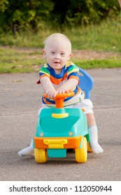 Portrait of a cute smiling baby boy with Down syndrome who driving a toy car