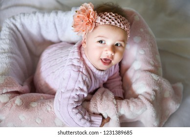 Portrait of cute smiling baby girl with a bow on her head, posing in pink clothes