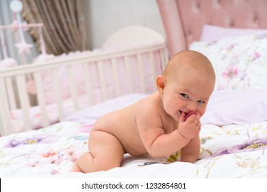 Portrait of a cute smiling baby without clothes on all fours on parents bed, with her pink cradle viewed in background