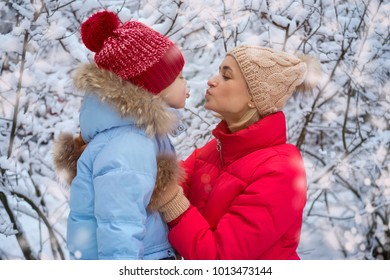 Portrait of cute a smiling boy and mother in winter forest