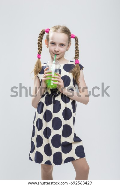 Portrait Of Cute And smiling Caucasian LIttle Girl With Pigtails Posing in Polka Dot Dress with Cup of Green Juice. Drinking Through Straw. Vertical Image