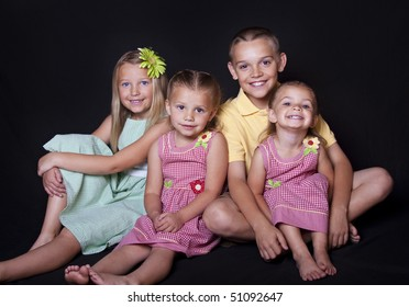Portrait of cute, smiling children on a black background.