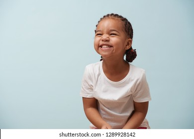 Portrait of cute smiling and giggling little girl dressed for sport. Pale blue background. Grin.