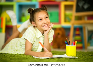 Portrait of cute smiling girl drawing at home