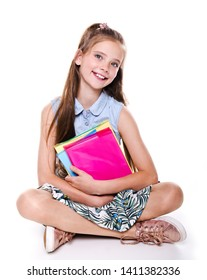 Portrait of cute smiling happy little school girl child teenager sitting on a floor and holding the books isolated on a white background education concept