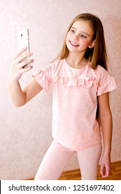 Portrait of cute smiling little girl child taking a selfie isolated over pink background