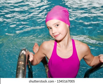 Portrait of cute smiling little girl child swimmer in pink swimming suit and cap in the swimming pool indoor