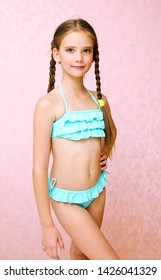 Portrait of cute smiling little girl child schoolgirl teenager in swimsuit isolated fashion concept