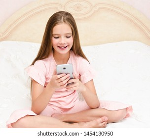 Portrait of cute smiling  little girl child playing with cell phone smartphone sitting no the bed at home