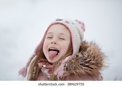 Portrait of cute smiling little girl in warm clothing catches snowflakes on your tongue