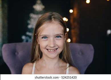Portrait of a cute smiling little girl on the background of Christmas decorations