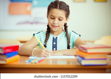 Portrait of cute smiling schoolgirl at school during lesson