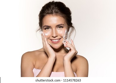 Portrait of cute smiling woman with foaming cleanser. Attractive joyful brunette looking at camera with happiness. Perfect fresh clean skin concept. Isolated on grey background