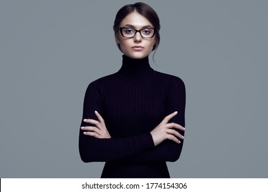 Portrait of cute student girl wearing black turtleneck sweater and stylish eyeglasses posing on gray background in studio