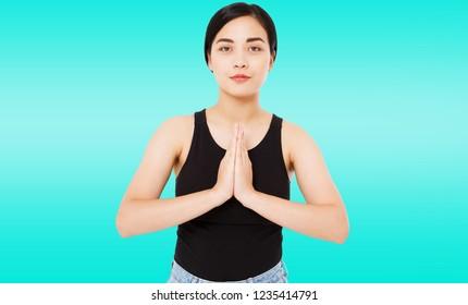 portrait of cute successful asian,korean woman shows namaste gesture on blue background, copy space,fitness joga concept