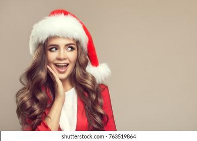 Portrait of cute surprised woman in santa hat. Christmas.