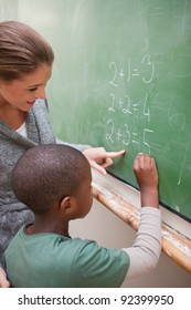 Portrait of a cute teacher and a pupil making an addition on a blackboard