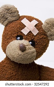 Portrait of a cute teddy bear with an adhesive bandage on forehead.