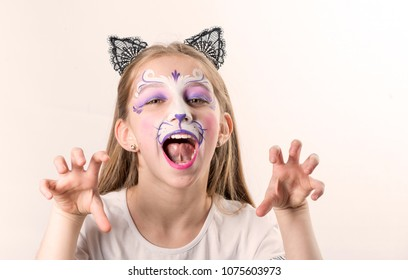 Portrait of cute teen girl with face painting of a cat posing in front of camera isolated on a white background