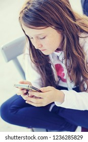 Portrait of cute teenage girl with mobile phone