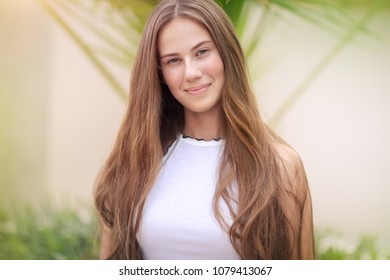 Portrait of a cute teenage girl outdoors over natural background, perfect appearance without makeup and with beautiful long natural hair, conceptual photo of beauty and freshness of youth
