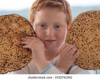 Portrait of the cute teenager boy holding matzah. Jewish child eating matzo unleavened bread in Jewish holidays Passover.