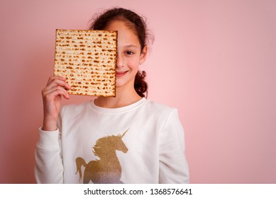 Portrait of the cute teenager girl holding matzah. Jewish child eating matzo unleavened bread in Jewish holidays Passover.