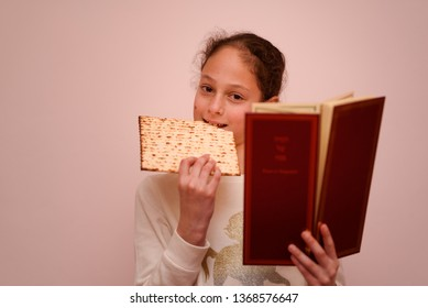 Portrait of the cute teenager girl holding matzah and reads the Passover Haggadah. Jewish child eating matzo unleavened bread in Jewish holidays Passover.