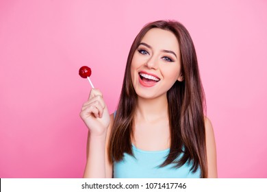 Portrait of cute tender gentle sweet attractive having fun carefree amazing woman wearing blue singlet holding red candy, isolated on vivid pink background