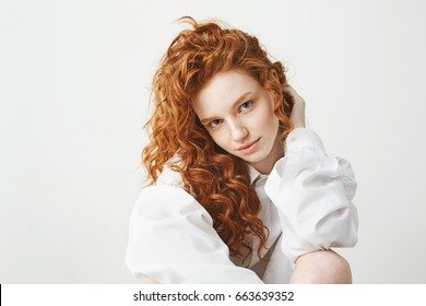 Portrait of cute tender ginger girl with curly hair looking at camera over white background.