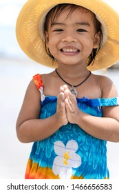 Portrait of cute Thai girl wearing a Hawaiian dress and straw hat on the beach. Little girl smiling  and Sawasdee is Thai national culture.