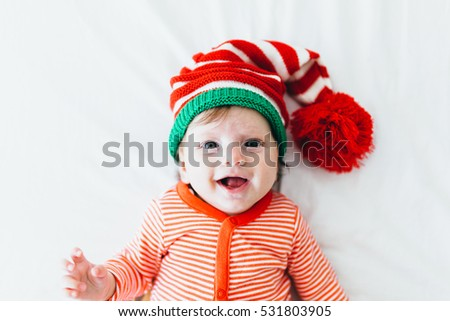 7ef77d4d414c Portrait of a cute three months old baby in Christmas hat lying on the  white blanket